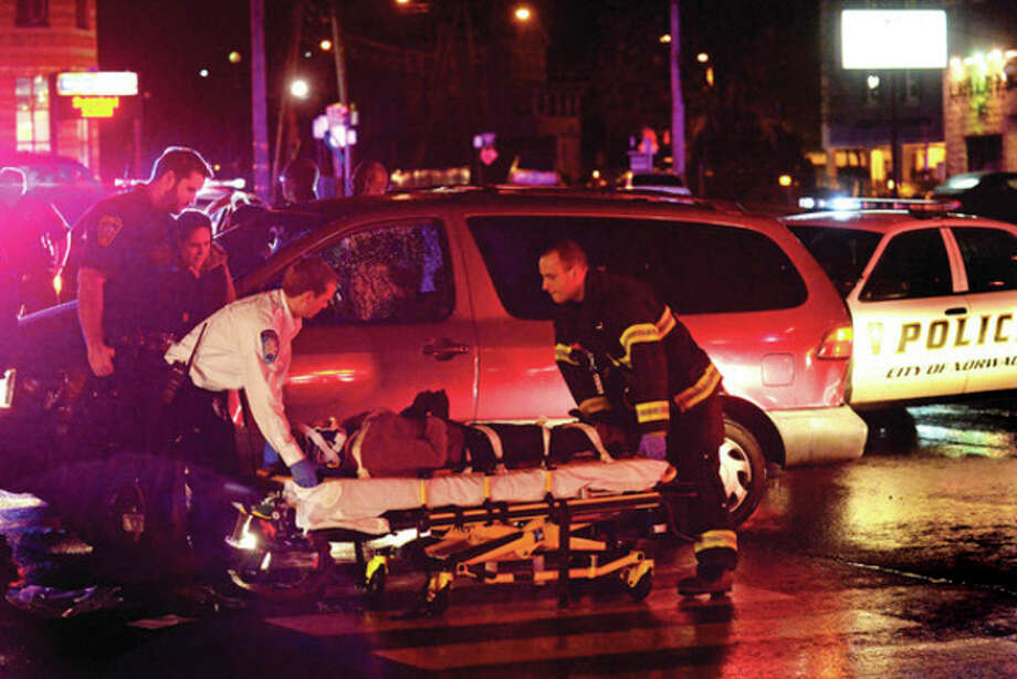 Hour photo / Erik TrautmannA woman is loaded onto a gurney after being hit by a motor vehicle at the intersection of West Cedar Street and Connecticut Avenue Friday night. / (C)2013, The Hour Newspapers, all rights reserved