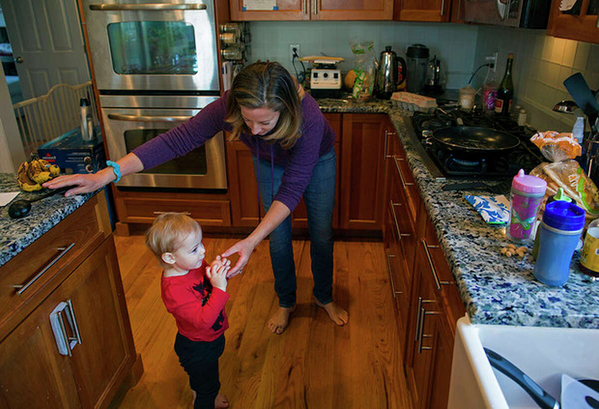 In this Nov. 23, 2013 photo, Carla Barzetti hands her daughter Grace, 2, an egg as she cooks breakfast at their Newtown, Conn. home. Carla says the family built their dream home on 18 acres here. But a tax hike, compounded by the divide over guns, convinced them they no longer belong. In September, they bought 150 acres in Tennessee and plan to move. Talking about it, she starts to cry, recalling Newtown before last Dec. 14.