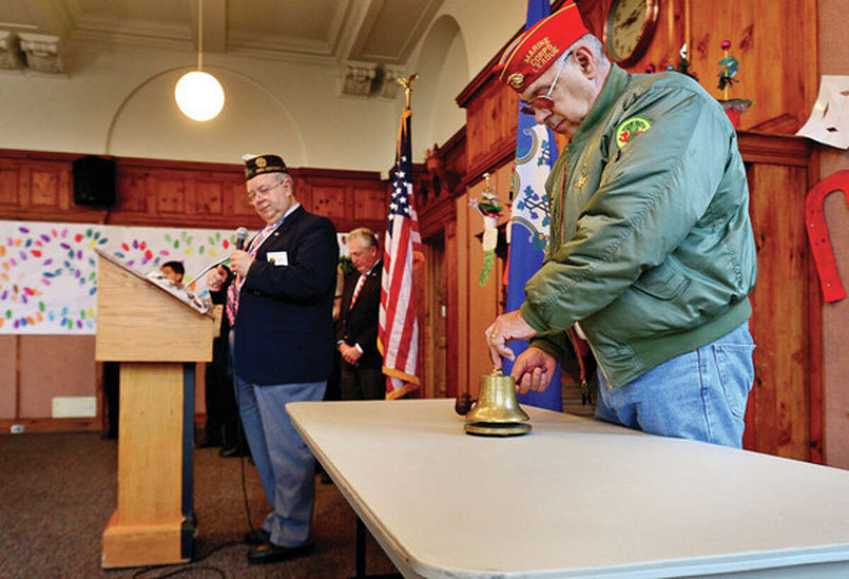 Hour photos / Erik Trautmann America Legion Post 12 Deputy Commander Rich Olsen reads the names of the Norwalk residents who died at Pearl Harbor as chairman of the Norwalk Veterans Memorial Committee Dan Caporale tolls the bell in remembrance during the city's Pearl Harbor Day ceremony in the Community Room at City Hall Saturday.