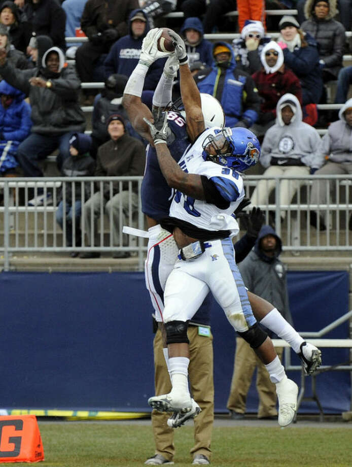 Connecticut wide receiver Geremy Davis (85) catches a touchdown pass over Memphis defensive back Reggis Ball (39) during the first half of an NCAA college football game in East Hartford, Conn., on Saturday, Dec. 7, 2013. (AP Photo/Fred Beckham)