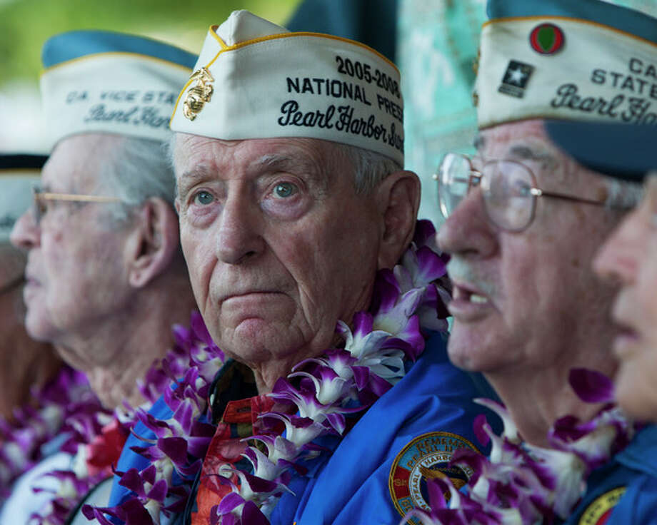 Pearl Harbor survivor Mal Middlesworth, center, sits with other Pearl Harbor survivors before the start of ceremony commemorating the 72nd anniversary of the attack on Pearl Harbor, Saturday, Dec. 7, 2013, in Honolulu. (AP Photo/Marco Garcia) / FR132415 AP
