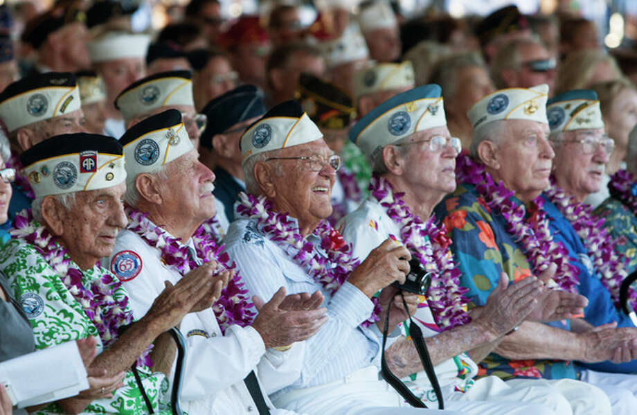 Pearl Harbor survivors watch a vintage WWII airplane fly over Pearl Harbor at the ceremony commemorating the 72nd anniversary of the attack on Pearl Harbor, Saturday, Dec. 7, 2013, in Honolulu. (AP Photo/Marco Garcia) / FR132415 AP