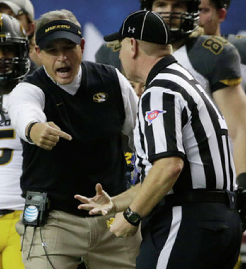 Missouri head coach Gary Pinkel speaks with an official during the second half of the Southeastern Conference NCAA football championship game against Auburn, Saturday, Dec. 7, 2013, in Atlanta. (AP Photo/Dave Martin) / AP