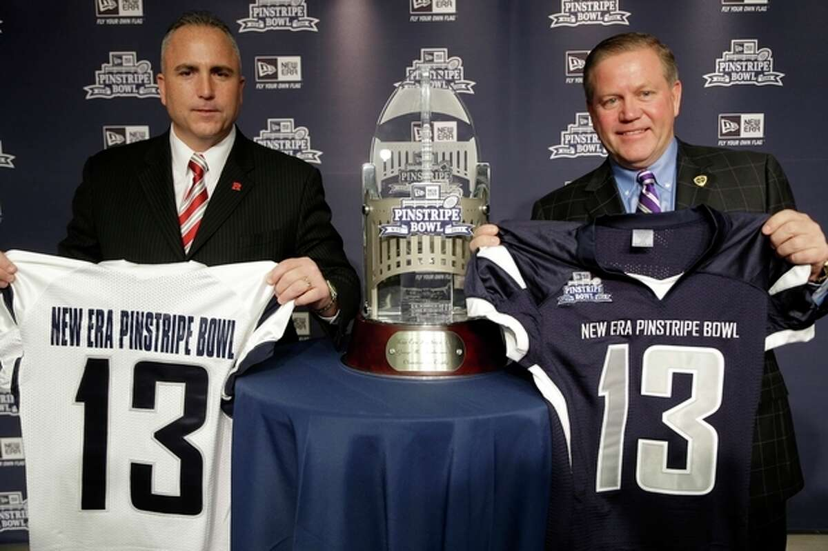Notre Dame coach Brian Kelly, right, and Rutger's coach Kyle Flood pose for pictures with the Pinstripe Bowl trophy during an NCAA college football news conference in New York, Tuesday, Dec. 10, 2013. Rutgers and Notre Dame will face off at the Pinstripe Bowl at Yankee Stadium on Saturday, Dec. 28, 2013. (AP Photo/Seth Wenig)