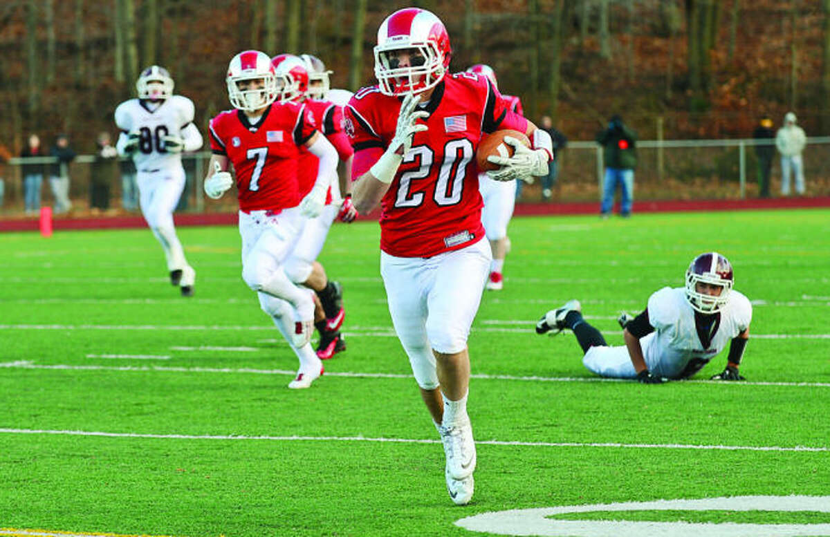Hour photo / Erik Trautmann Kyle Smith of New Canaan runs to set up a field goal in their game against North Haven Saturday during the semi final championships in Milford.