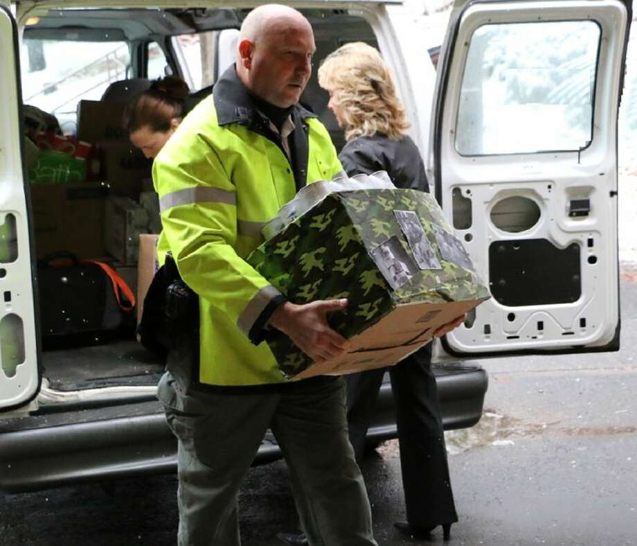 Heroes and Hounds founder Mark Rudewicz of Simsbury and Best Friends employees unload more than $5,000 in supplies for holiday care packages headed to canine military teams serving in Iraq and Afghanistan.  (Photo by Jen Tobias)