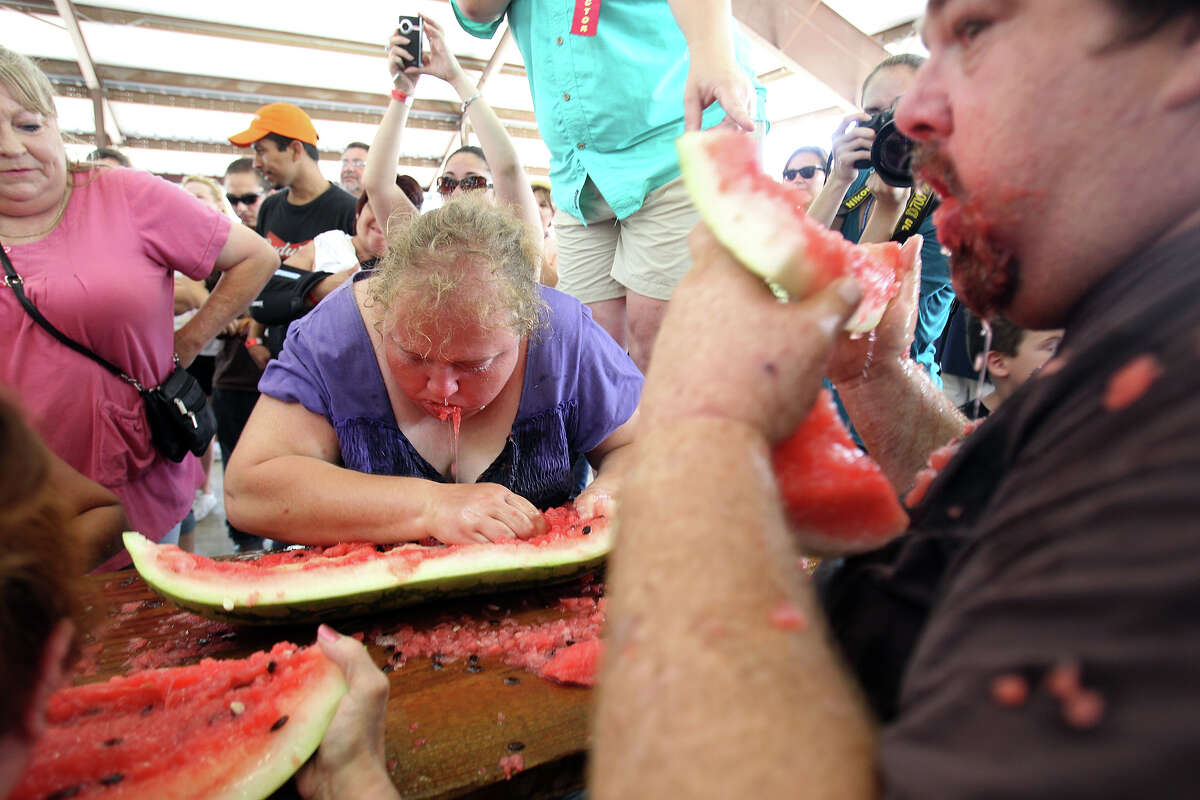 Danielle Harris, center, works at her rind as Ray Mayer, right, lifts his to declare 3rd place in the adult watermelon eating competition at the Luling Watermelon Thump, Saturday, June 26, 2010. (Jennifer Whitney/ special to the San Antonio Express-News)