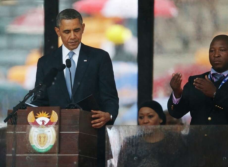 President Barack Obama looks down as he stands next to the sign language interpreter as he makes his speech at the memorial service for former South African president Nelson Mandela at the FNB Stadium in Soweto near Johannesburg, Tuesday, Dec. 10, 2013. South Africa's deaf federation said on Wednesday that the interpreter on stage for Mandela memorial was a 'fake', (AP Photo/Matt Dunham) / AP