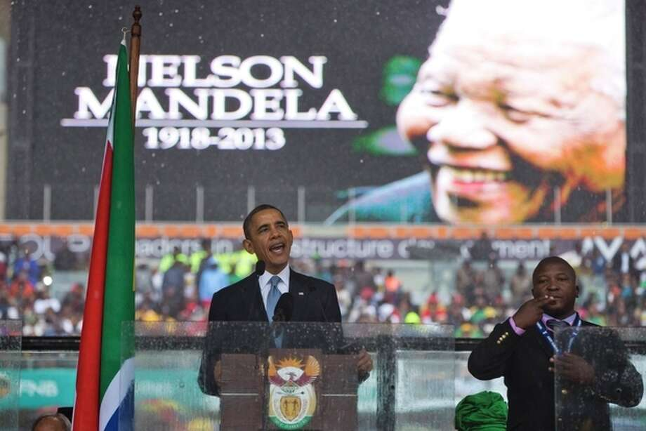 """President Barack Obama delivers his speech next to a sign language interpreter during a memorial service at FNB Stadium in honor of Nelson Mandela on Tuesday, Dec. 10, 2013 in Soweto, near Johannesburg. The national director of the Deaf Federation of South Africa says a man who provided sign language interpretation on stage for Nelson Mandela's memorial service in a soccer stadium was a """"fake.""""(AP Photo/ Evan Vucci) / AP"""