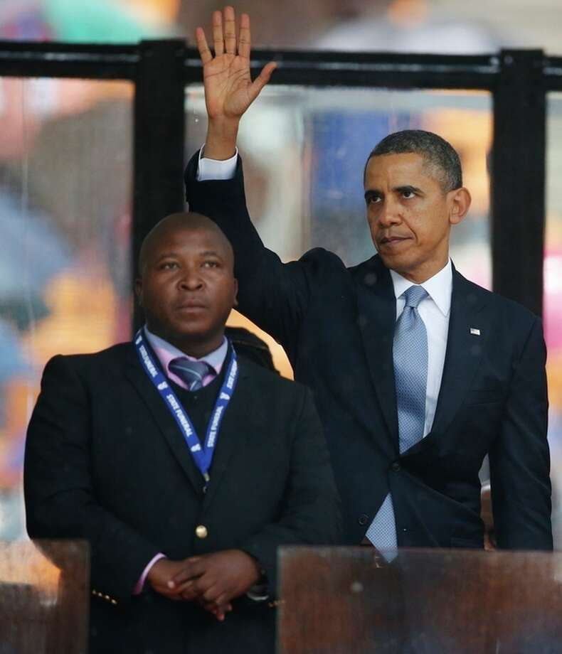 President Barack Obama waves standing next to the sign language interpreter after making his speech at the memorial service for former South African president Nelson Mandela at the FNB Stadium in Soweto near Johannesburg, Tuesday, Dec. 10, 2013. South Africa's deaf federation said on Wednesday that the interpreter on stage for Mandela memorial was a 'fake', (AP Photo/Matt Dunham) / AP