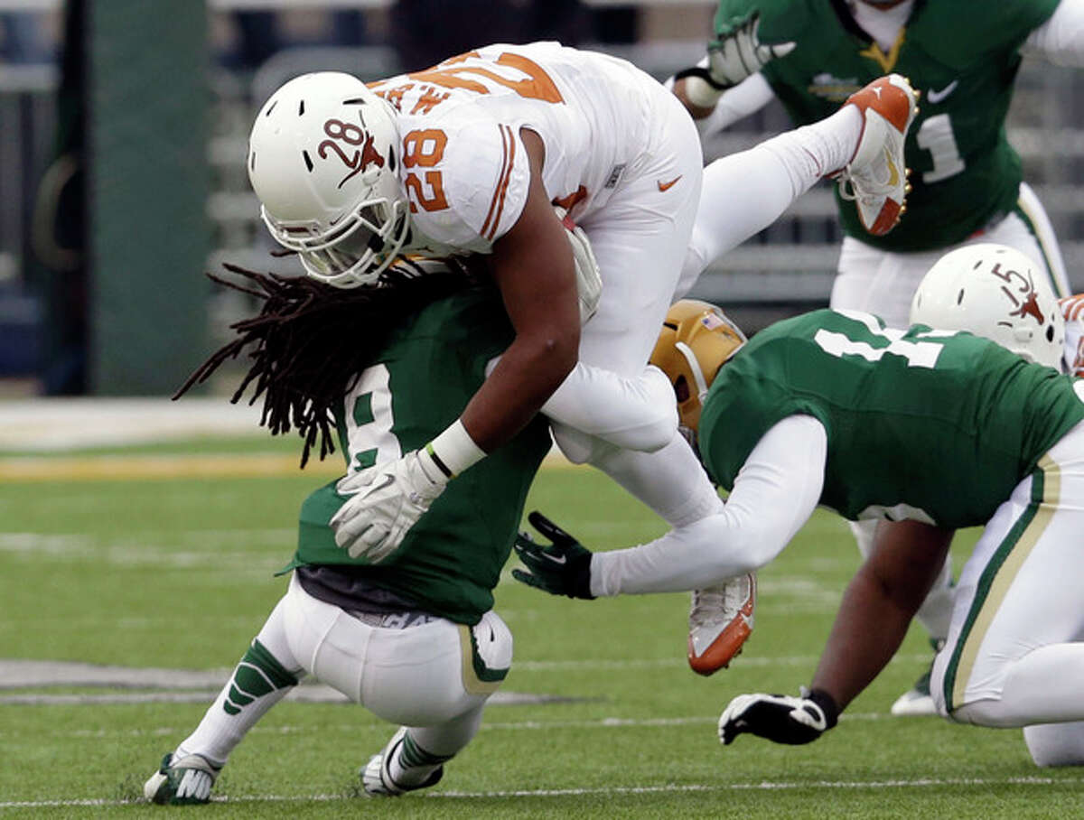 Texas running back Malcolm Brown (28) is stopped by Baylor's K.J. Morton (8) and Brody Trahan (15) during the first half of an NCAA college football game on Saturday, Dec. 7, 2013, in Waco, Texas. (AP Photo/LM Otero)