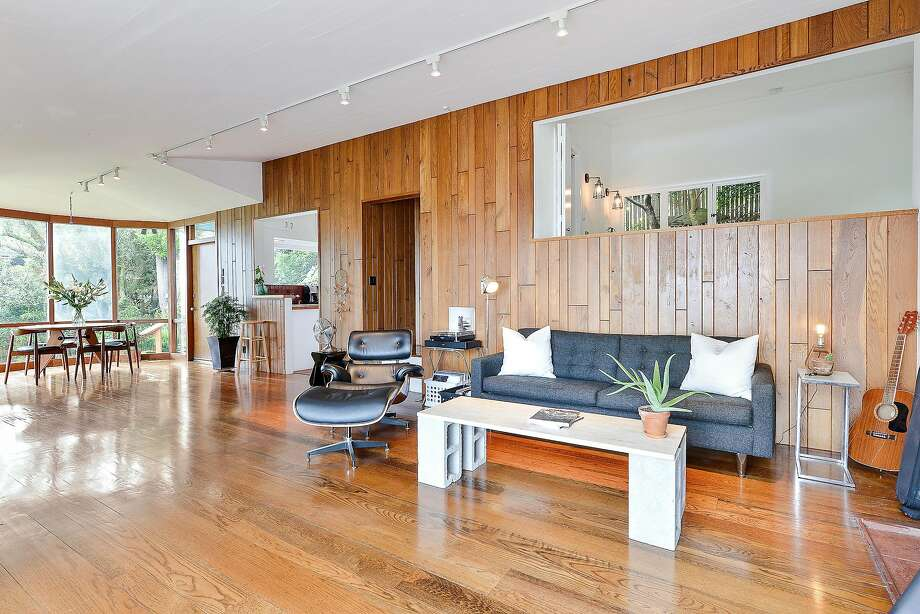 A wood-paneled accent wall spans the length of a spacious living/dining room. Photo: OpenHomesPhotography