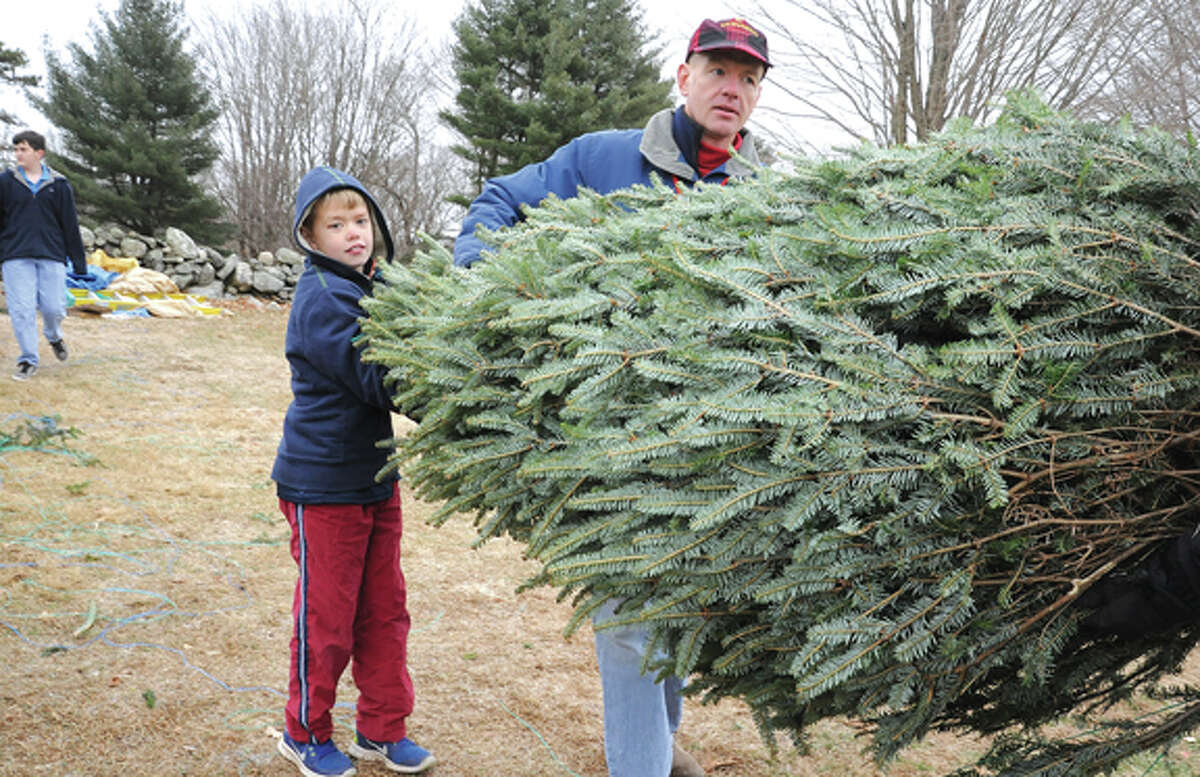 Jim Keneon and his son Ian 10, carry out thier new Christmas Tree Sunday at Amber Farm's green sale in Wilton. Hour photo/Matthew Vinci