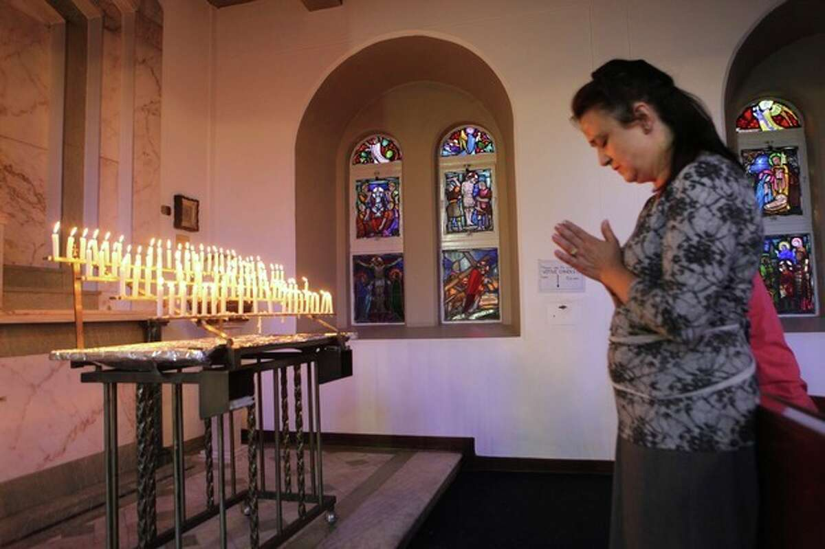 A woman prays during a church service in honour of Nelson Mandela in Johannesburg, South Africa, Sunday, Dec. 8, 2013. People in South Africa are taking part in a day of