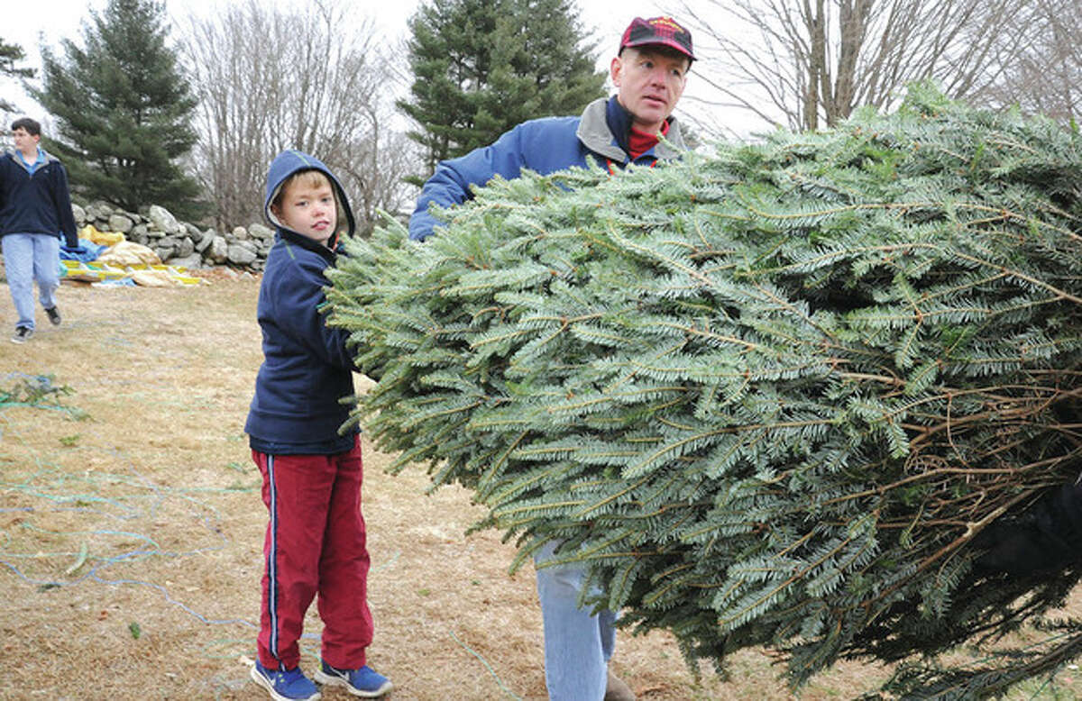 Hour photo / Matthew Vinci Jim Keneon and his son Ian, 10, carry out their new Christmas tree Sunday at Amber Farm's green sale in Wilton.