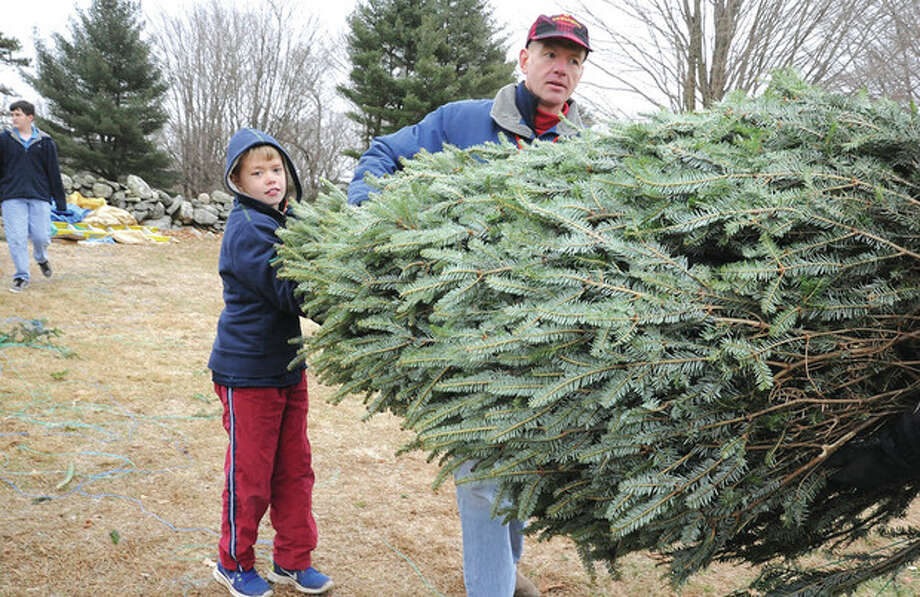 Hour photo / Matthew VinciJim Keneon and his son Ian, 10, carry out their new Christmas tree Sunday at Amber Farm's green sale in Wilton.