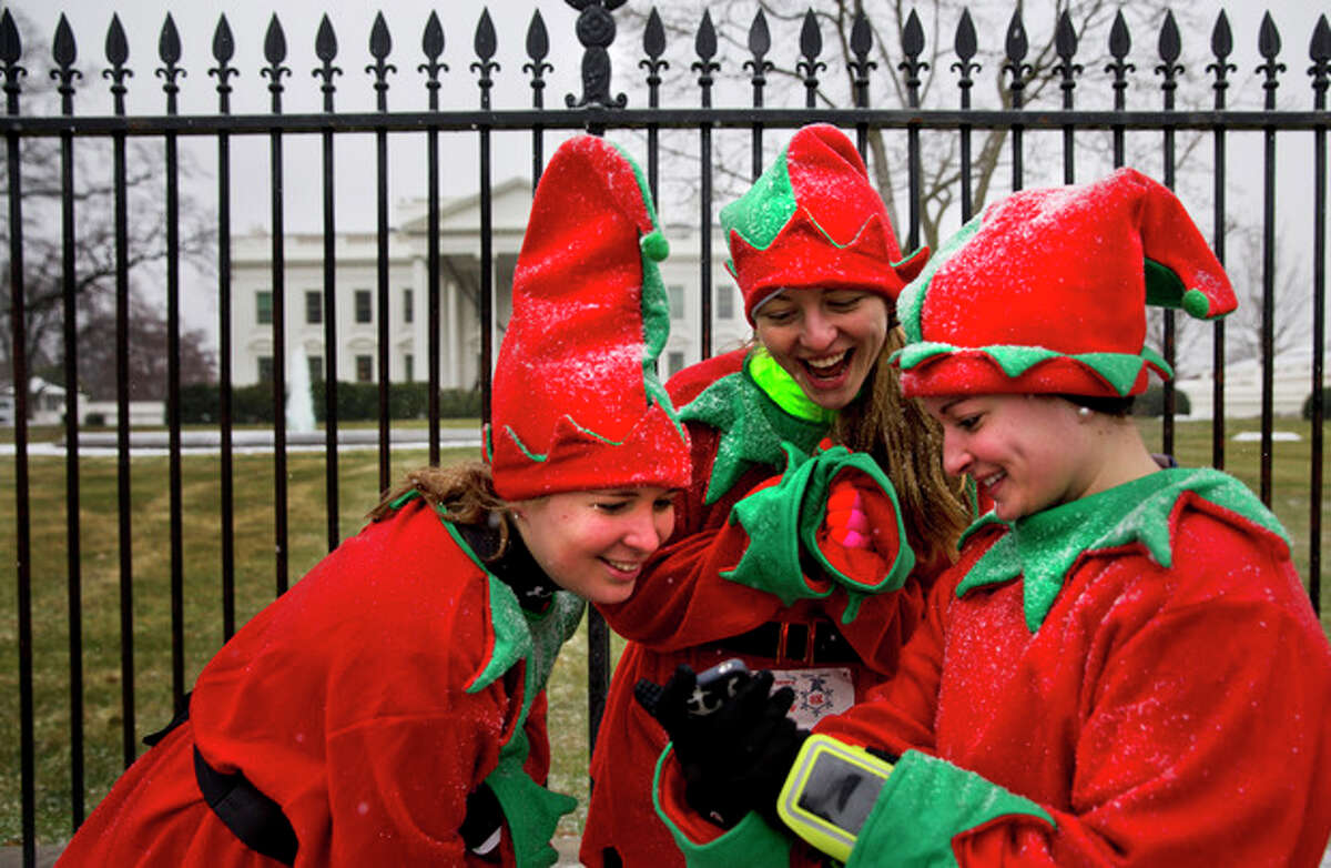 A light snow falls as Meryl Dann, left, Michelle Kalicki, and Abigail Walsh react while looking at a cell phone photo of themselves in their elf costumes by the White House in Washington, Sunday, Dec. 8, 2013. The college students stopped by the White House after participating in the