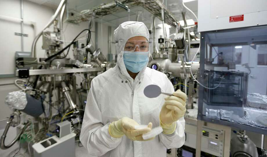 Stephanie Chastang, a Wafer Process Engineer, holds an Indium Phosphide wafer used to make chips for laser products as she stands in front of the MBE system (a Molecular Beam Epitaxy) used to grow materials for semiconductor lasers in the production facility at Applied Optoelectronics Tuesday, May 10, 2016, in Houston.  The company ranks No. 5 on the Chronicle 100 public companies list. The company is a provider of fiber-optic networking products. Photo: Karen Warren, Houston Chronicle / © 2016 Houston Chronicle
