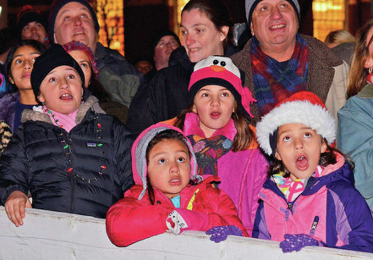Hour photo / Harold Cobin Children appear awestruck Sunday evening by the sight of Santa Claus rappelling down the outside of the Landmark Square building on Broad Street.