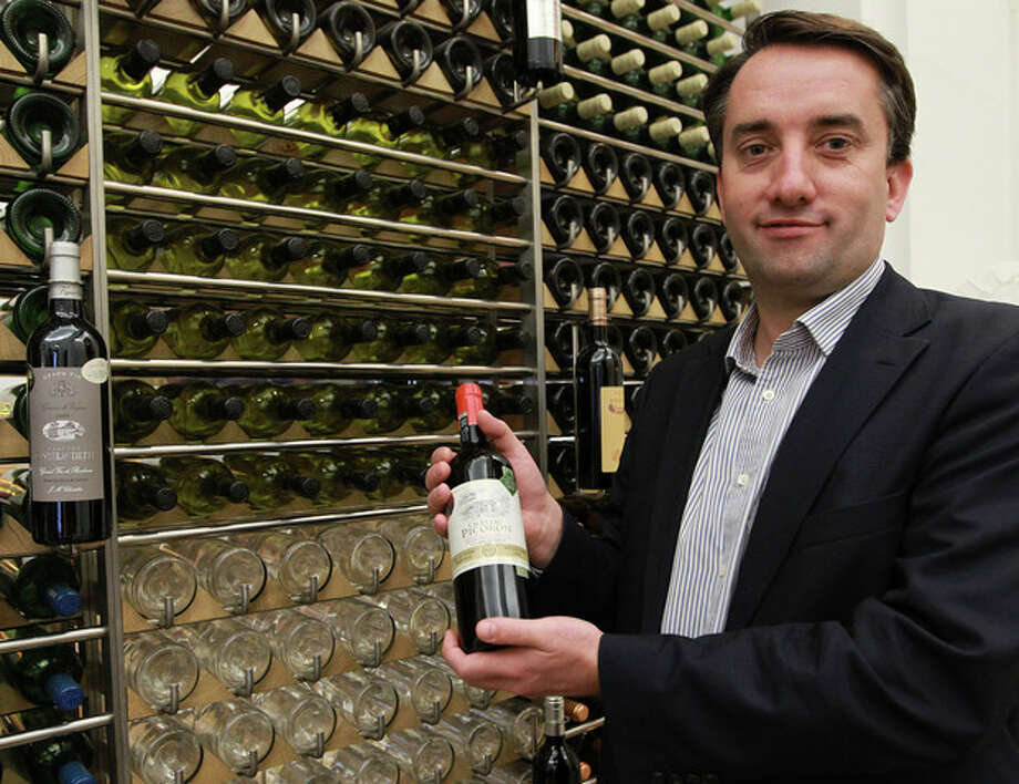 In this photo dated Wednesday, Nov. 13, 2013, Christophe chateau, head of the communication of the Bordeaux winegrower's professional association displays a bottle of wine at his office in Bordeaux, southwestern France. Counterfeiting has dogged wine as long as it has been produced, but it is getting more sophisticated and more ambitious, particularly as bottle prices rise due to huge demand in new markets, mainly in Asia. (AP Photo/Bob Edme) / AP