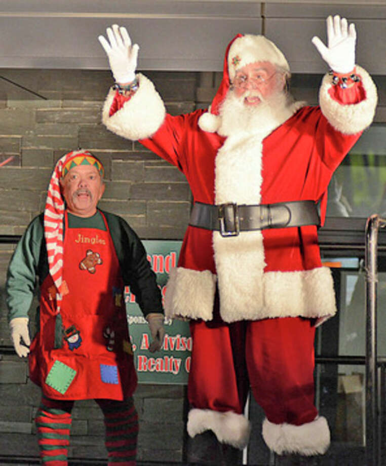 Santa Claus gestures toward the hundreds of spectators who turned out Sunday evening to watch him rappel down the side of the Landmark Square building on Broad Street.