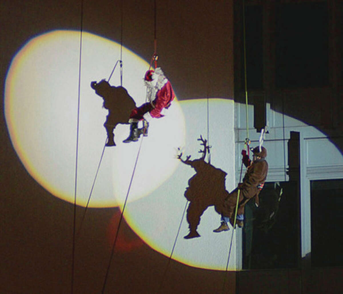 Hour photos / Harold Cobin At left, Santa Claus gestures toward the hundreds of spectators who turned out Sunday evening to watch him rappel down the side of the Landmark Square building on Broad Street. At right, Santa rappels down with his lead reindeer,