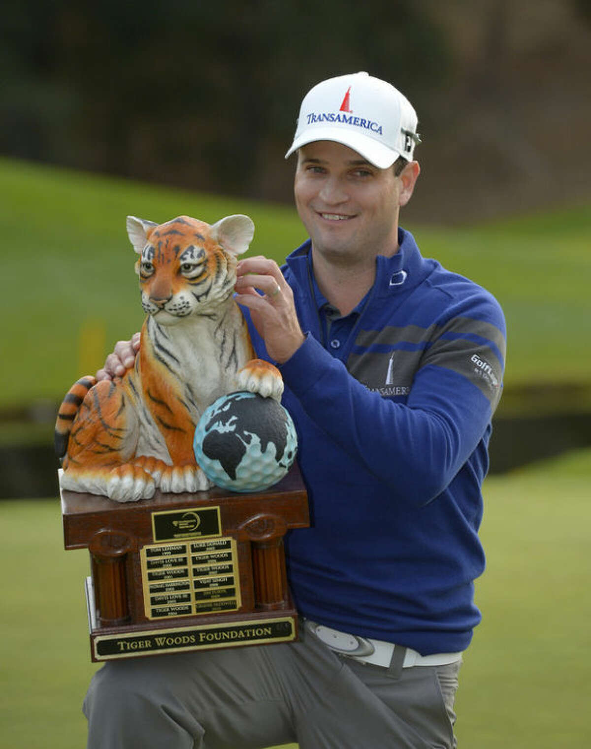 Zach Johnson scratches the head of the tiger on the trophy after winning a playoff against Tiger Woods in the final round of the Northwestern Mutual World Challenge golf tournament at Sherwood Country Club, Sunday, Dec. 8, 2013, in Thousand Oaks, Calif. (AP Photo/Mark J. Terrill)