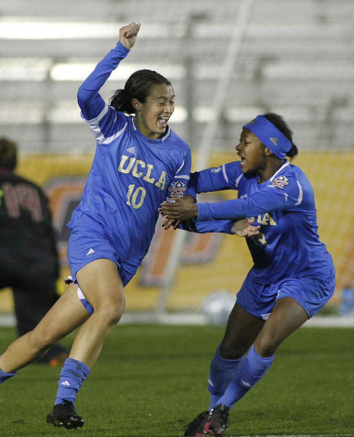 UCLA'S Kodi Lavrusky, left, celebrates with teammate Taylor Smith, right, after scoring the winning goal against Florida State in overtime of the championship soccer game at the NCAA Women's College Cup in Cary, N.C., Sunday, Dec. 8, 2013. (AP Photo/Ellen Ozier)