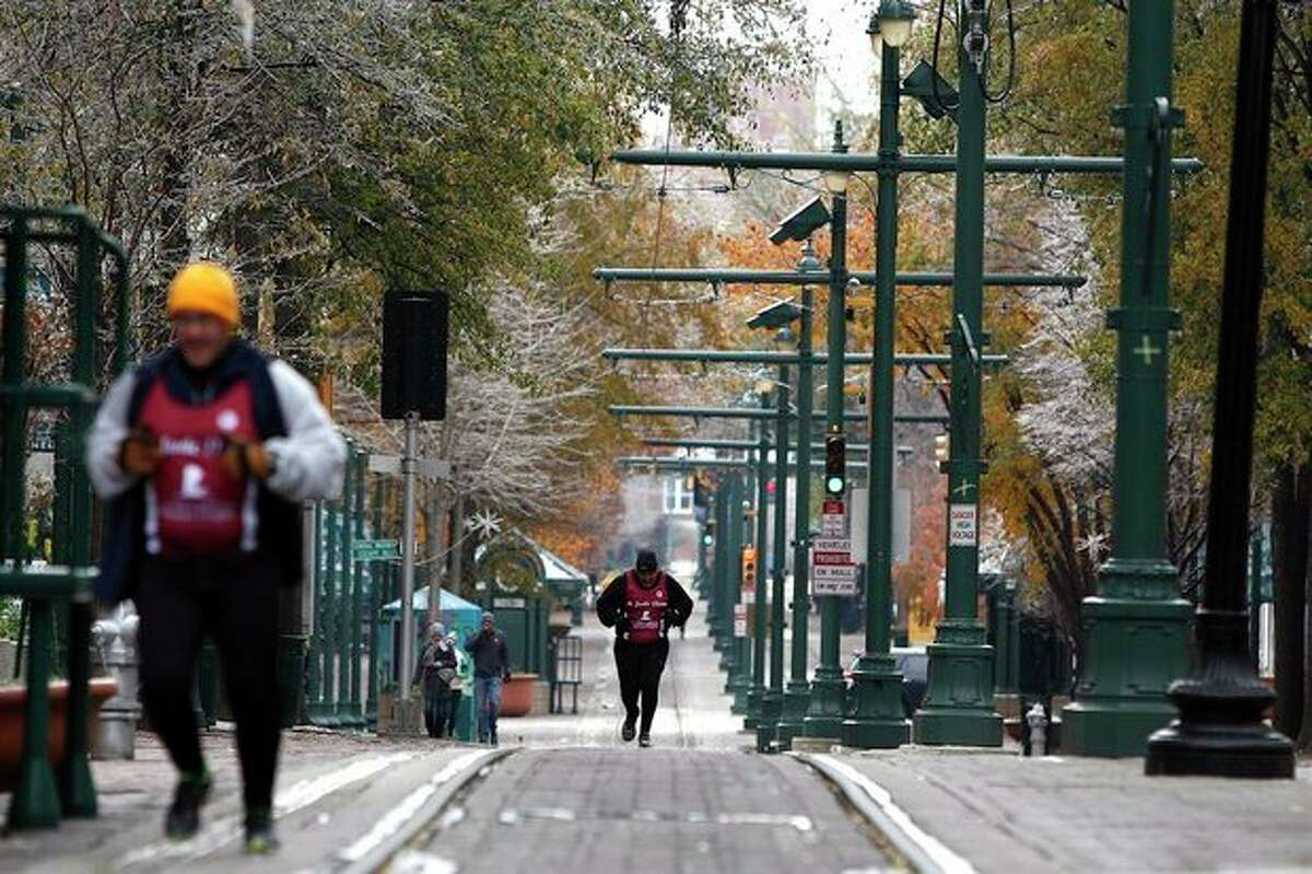 A runner makes his way down Main Street, despite the cancellation of the St. Jude Memphis Marathon, in Memphis, Tenn. Saturday, Dec. 7, 2013. The weather forced the cancellation of the marathon, which expected to include 20,000 runners. (AP Photo/The Commercial Appeal, William DeShazer)