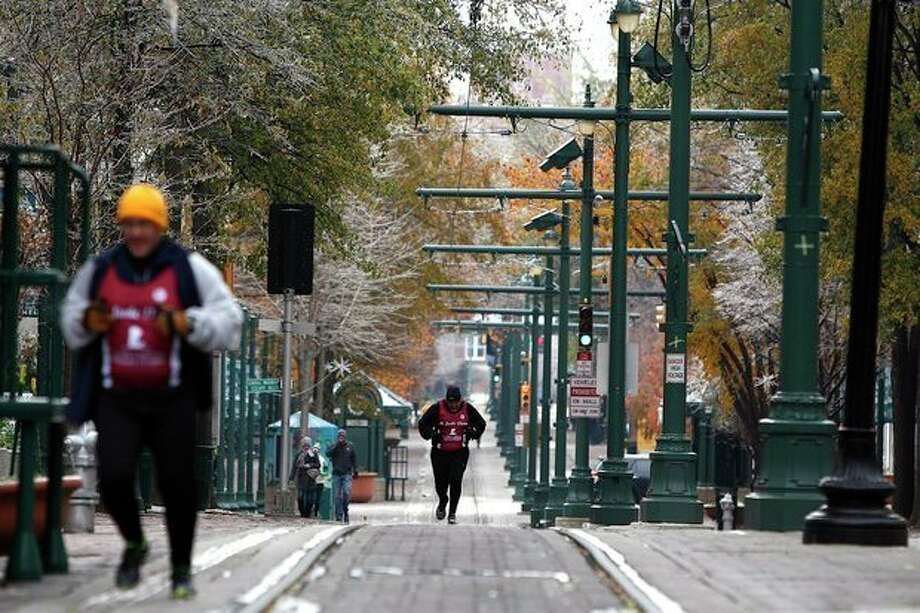 A runner makes his way down Main Street, despite the cancellation of the St. Jude Memphis Marathon, in Memphis, Tenn. Saturday, Dec. 7, 2013. The weather forced the cancellation of the marathon, which expected to include 20,000 runners. (AP Photo/The Commercial Appeal, William DeShazer) / The Commercial Appeal