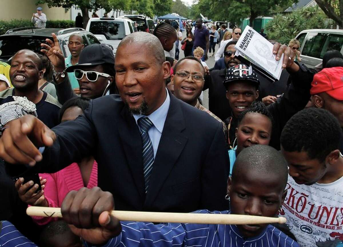 Grandson Mandla Mandela, marches with people outside his grandfather, former president Nelson Mandela's home in Johannesburg, South Africa, Monday, Dec. 9, 2013. Scores of heads of state and government and other foreign dignitaries, including royalty, are beginning to converge on South Africa as the final preparations for Tuesday's national memorial service for liberation struggle icon Nelson Mandela are put in place. (AP Photo/Themba Hadebe)