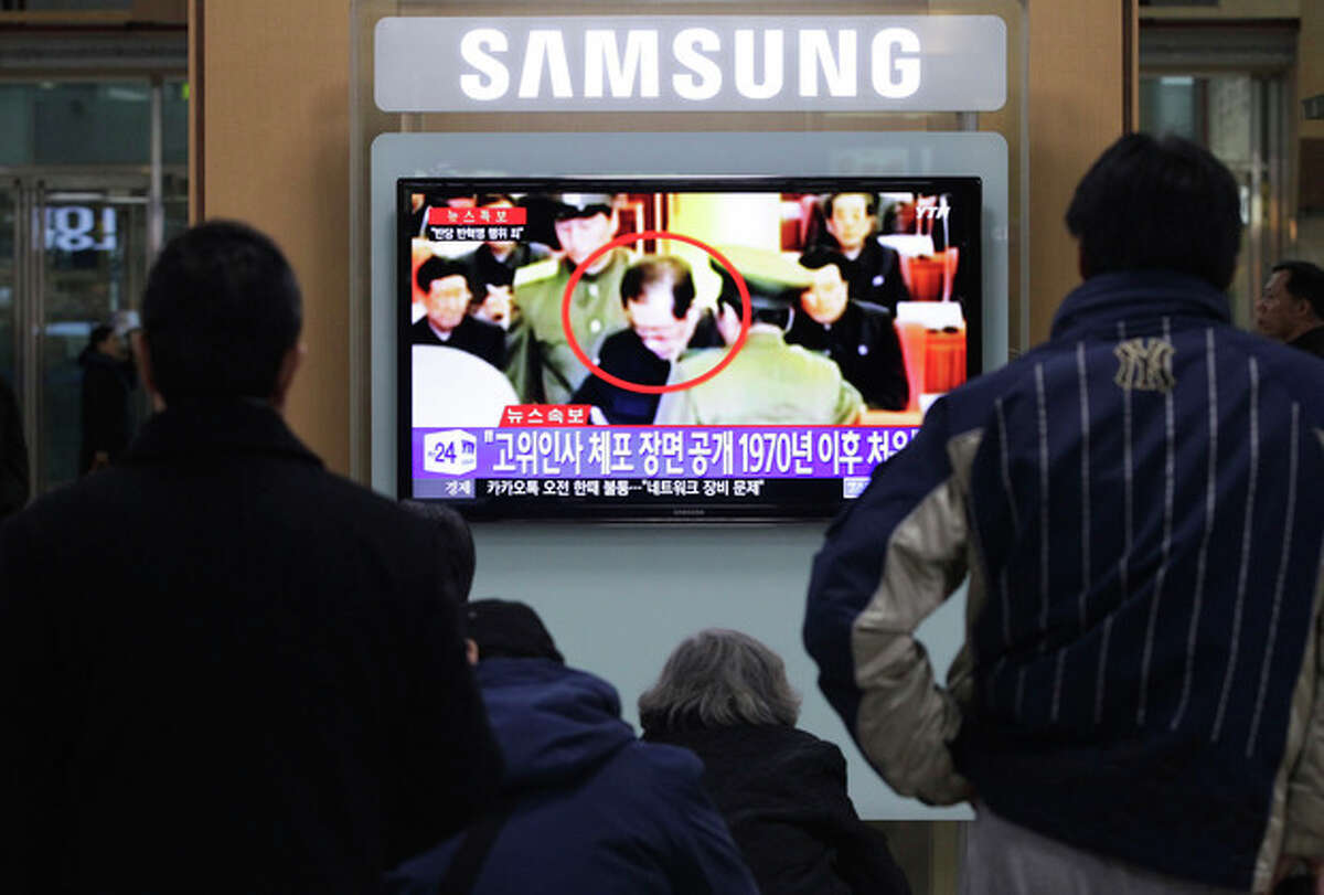 People watch a TV news program at Seoul Railway Station, South Korea, Monday, Dec. 9, 2013 showing Jang Song Thaek, center, uncle of North Korean leader Kim Jong Un, being grabbed during an emergency meeting of Workers Party's Central Committee in Pyongyang the day before. North Korea announced Monday it had sacked leader Jang, long considered the country's No. 2 power, saying corruption, drug use, gambling, womanizing and generally leading a