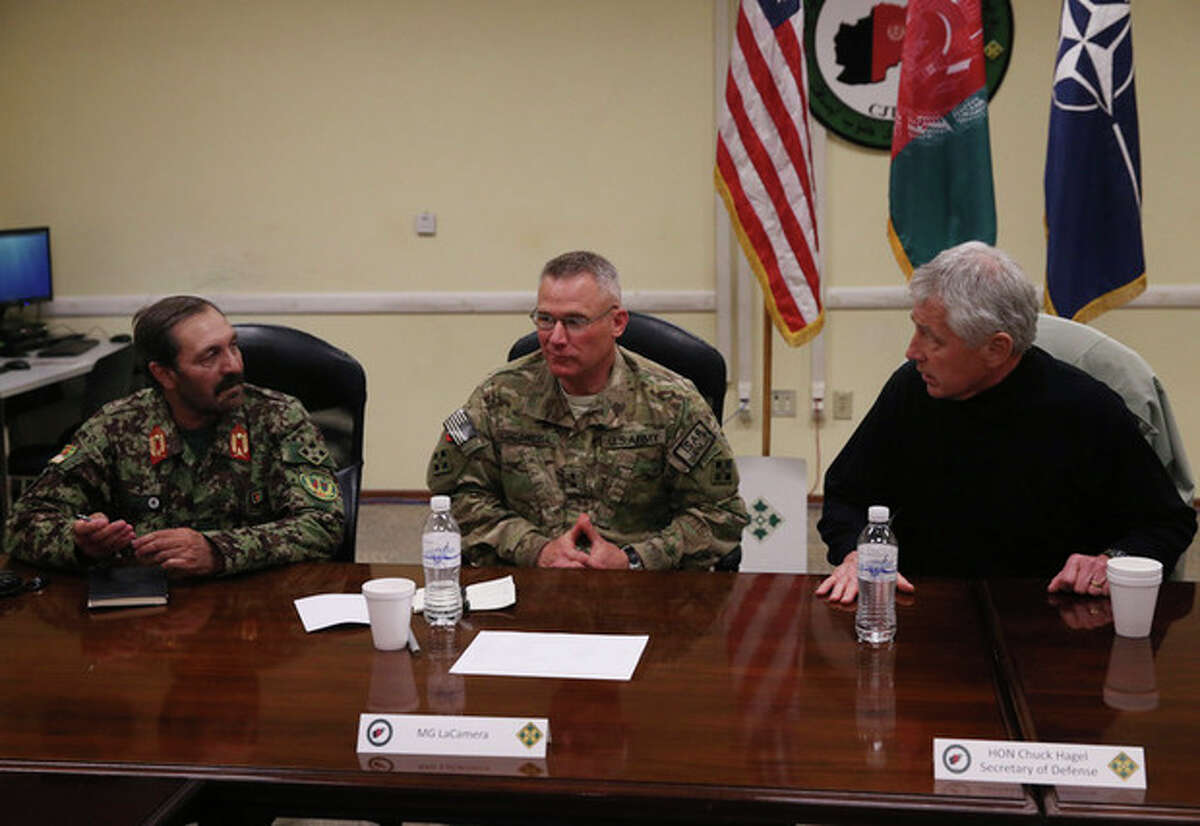 U.S. Secretary of Defense Chuck Hagel, right, speaks with Hamid Abdul Hamid, left, and MaJ. Gen Paul La Camera, center, during a meeting with Afghan military leaders in Kandahar, Afghanistan, Sunday, Dec. 8, 2013. Hagel spoke with U.S. troops and thanked them for being deployed for the holidays. (AP Photo/Mark Wilson, Pool)