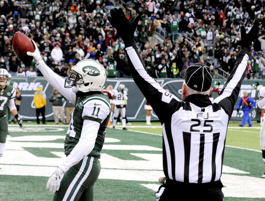 New York Jets wide receiver Jeremy Kerley (11) holds the football after making a touchdown catch on a pass from Jets quarterback Geno Smith as field judge Bob Waggoner (25) signals for the score during the first half of an NFL football game against the Oakland Raiders, Sunday, Dec. 8, 2013, in East Rutherford, N.J. (AP Photo/Bill Kostroun) / FR51951 AP