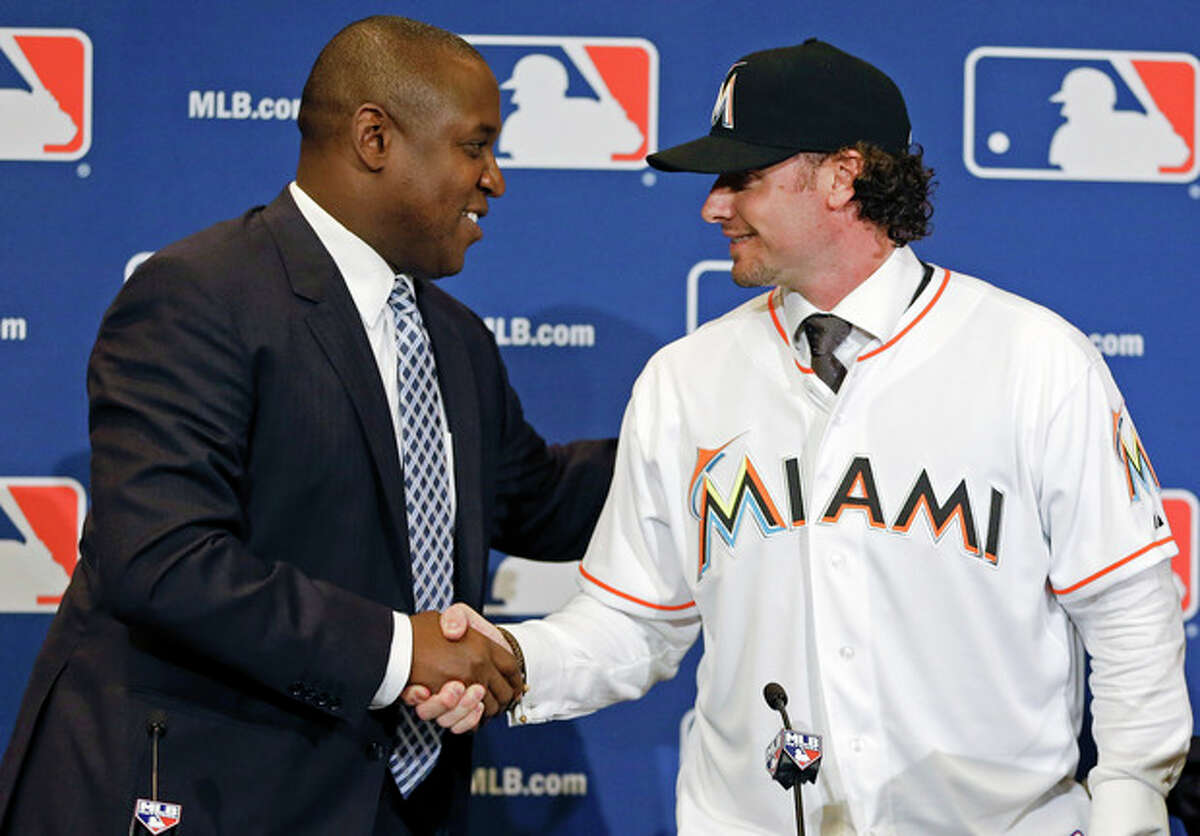 Michael Hill, left, president of baseball operations for the Miami Marlins shakes hands with Jarrod Saltalamacchia welcoming him to the team during a news conference at the MLB winter meetings in Lake Buena Vista, Fla., Monday, Dec. 9, 2013. Saltalamacchia signed a 3-year deal with the Marlins. (AP Photo/John Raoux)