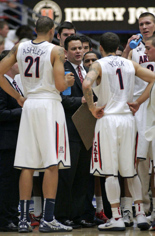 Arizona's head coach Sean Miller, center, talks to Brandon Ashley (21) and Gabe York (1) in a team huddle during a timeout against UNLV in the first half of an NCAA college basketball game on Saturday, Dec. 7, 2013, in Tucson, Ariz. Arizona won 63-58. (AP Photo/John MIller)