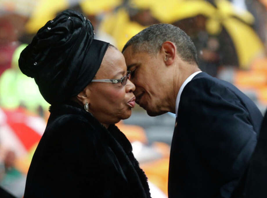President Barrack Obama kisses Nelson Mandela's widow Graca Machel during the memorial service for former South African president Nelson Mandela at the FNB Stadium in Soweto near Johannesburg, Tuesday, Dec. 10, 2013. (AP Photo/Matt Dunham) / AP