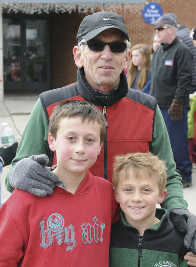 Photo by Tim DowneyTom Kretsch, the founder of the Norwalk River Fun Run, stands with two of this year's participants, Benjamin Vitenson, left, and his brother Julian, a student at Rowayton Elementary School, near the finish line of Saturday's 23rd annual event for young runners and their families.