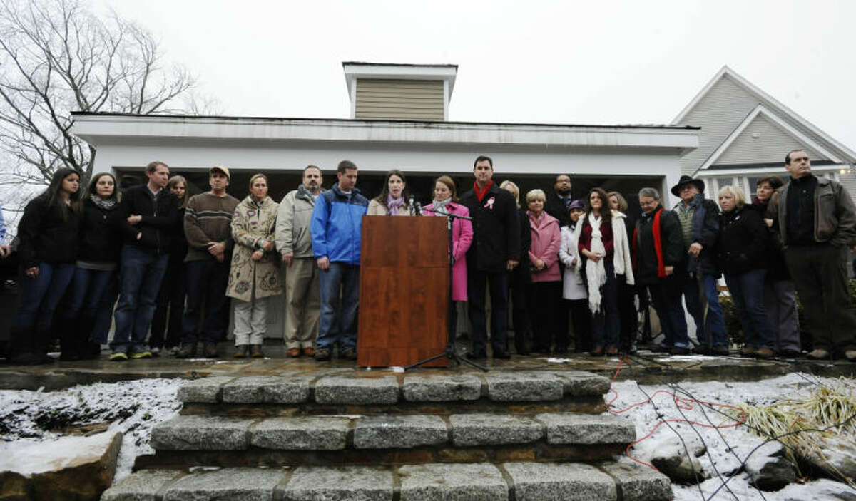 Family members representing fourteen of the twenty-six victims from the Sandy Hook Elementary School shooting address the media, Monday, Dec. 9, 2013, in Newtown, Conn. Newtown is not hosting formal events to mark the anniversary Saturday. (AP Photo/Jessica Hill)