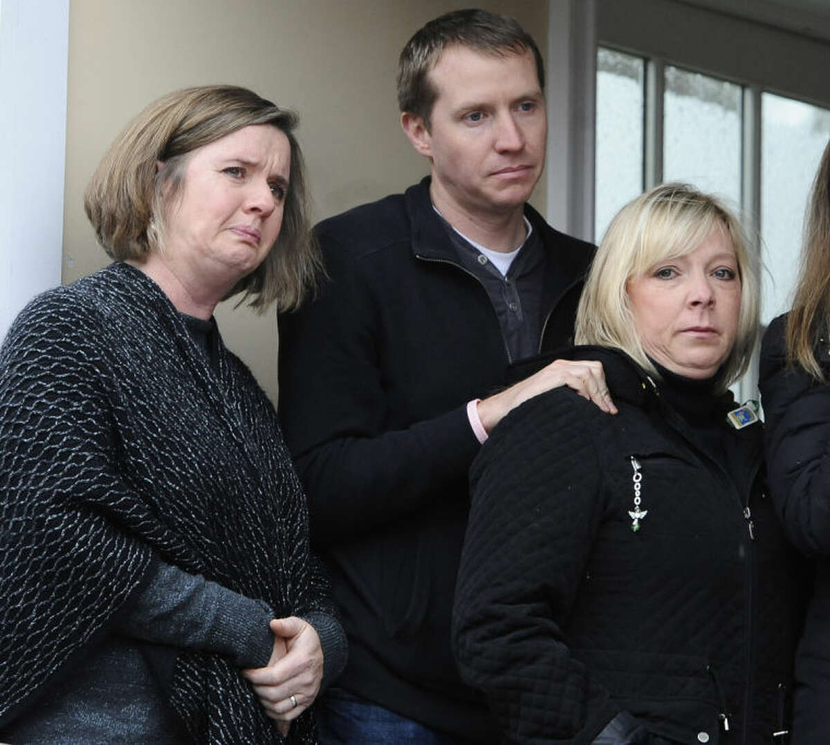 Jackie Barden, mother of Sandy Hook School shooting victim Daniel Barden, Robbie Parker, father of victim Emilie Parker, and Joy Rousseau, relative of victim Lauren Rousseau, stand with other family members as they address the media, Monday, Dec. 9, 2013, in Newtown, Conn. Newtown is not hosting formal events to mark the anniversary Saturday. (AP Photo/Jessica Hill)