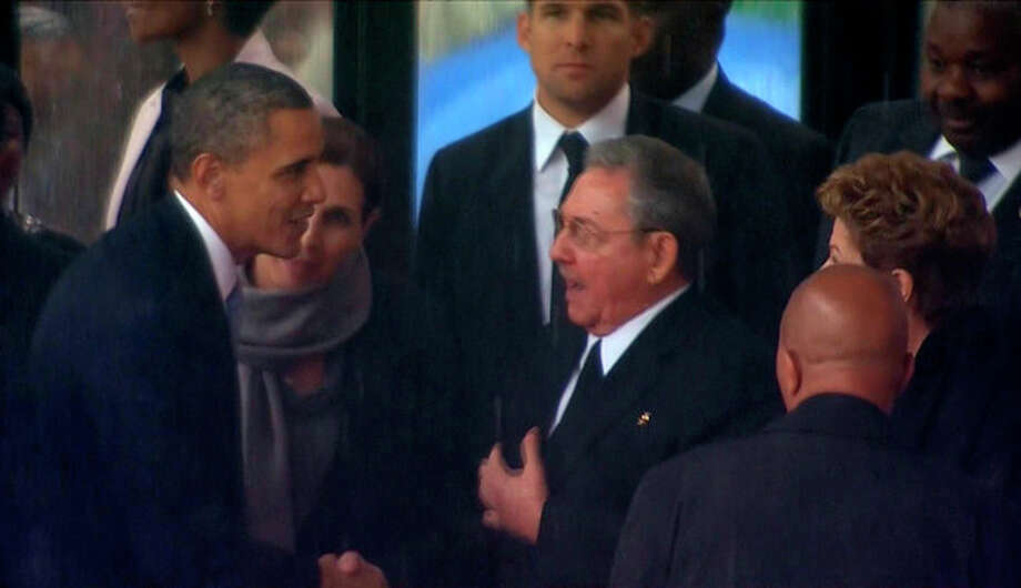In this image from TV, US President Barack Obama shakes hands with Cuban President Raul Castro at the FNB Stadium in Soweto, South Africa, in the rain for a memorial service for former South African President Nelson Mandela, Tuesday Dec. 10, 2013. The handshake between the leaders of the two Cold War enemies came during a ceremony that's focused on Mandela's legacy of reconciliation. Hundreds of foreign dignitaries and world heads of states gather Tuesday with thousands of South African people to celebrate the life, and mark the death, of Nelson Mandela who has became a global symbol of reconciliation. (AP Photo/SABC Pool) / pool sabc