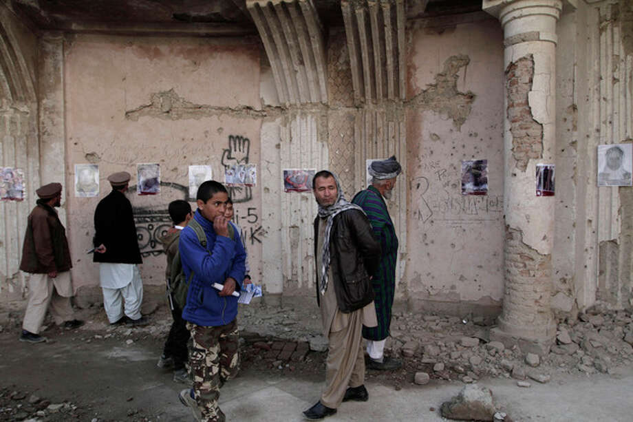 Afghans look at photographs in an exhibition set up at the palace of the late King Amanullah Khan in Kabul, Afghanistan, Tuesday, Dec. 10, 2013. The photo exhibition organized by the Social Association of Afghan Justice Seekers featured portraits of war victims of the last three decades in Afghanistan, to mark the U.N.'s Human Rights Day. (AP Photo/Rahmat Gul) / AP