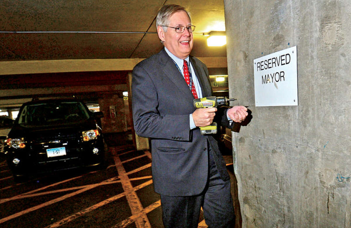 Mayor David Martin announces a Government Center parking plan to make government more accessible to residents. The parking overhaul will move reserved staff spaces, including his, to the other floors of the garage and open spaces to the public on the ground floor. Above, Martin removes the sign designating the mayor's parking space during a press conference at the Government Center on Friday.