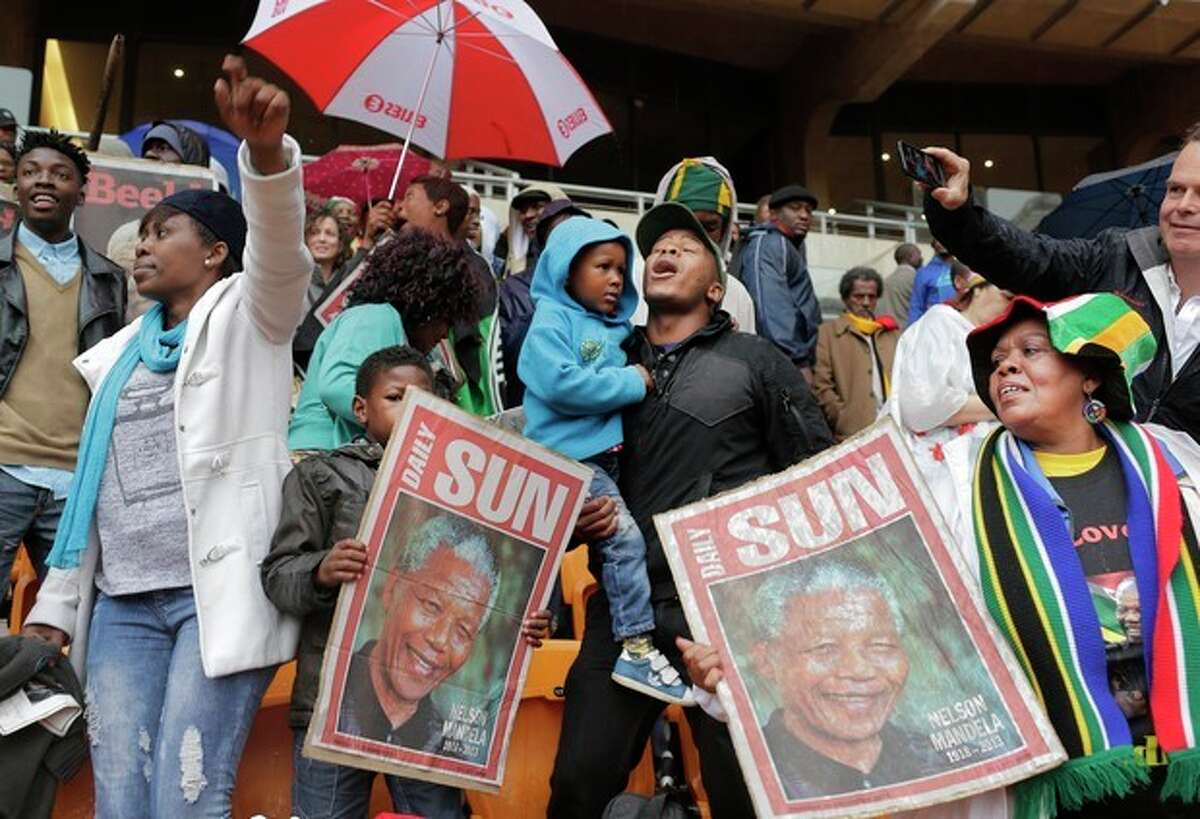 People hold images of former South African president Nelson Mandela ahead of his memorial service at the FNB Stadium in Soweto, near Johannesburg, South Africa, Tuesday Dec. 10, 2013. (AP Photo/Bernat Armangue)