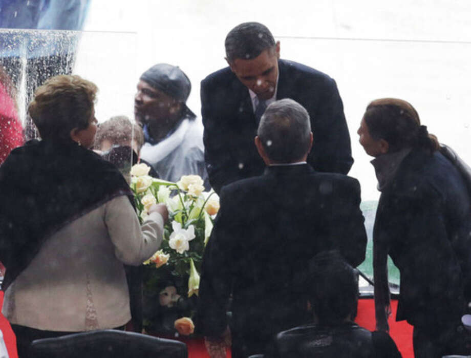 Brazil's President Dilma Rousseff, left, watches as President Barack Obama shakes hands with Cuba's President Raul Castro Ruz during the memorial service for former South African president Nelson Mandela at the FNB Stadium in Soweto near Johannesburg, Tuesday, Dec. 10, 2013. (AP Photo/Markus Schreiber) / AP