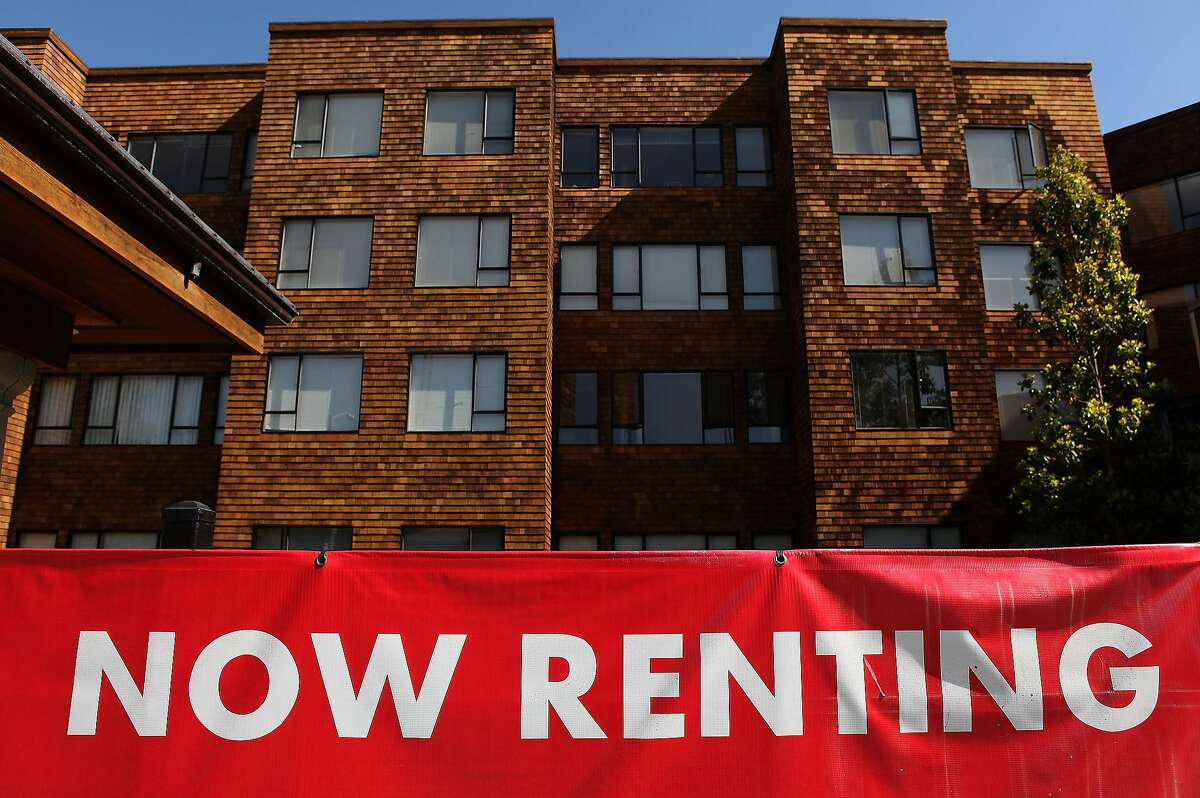 A sign advertising apartments for rent is displayed in front of an apartment complex in San Francisco.