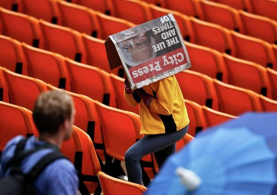 A woman covers herself from the rain as she arrives for the memorial service for former South African president Nelson Mandela at the FNB Stadium in Soweto, near Johannesburg, South Africa, Tuesday Dec. 10, 2013. (AP Photo/Ben Curtis) / AP