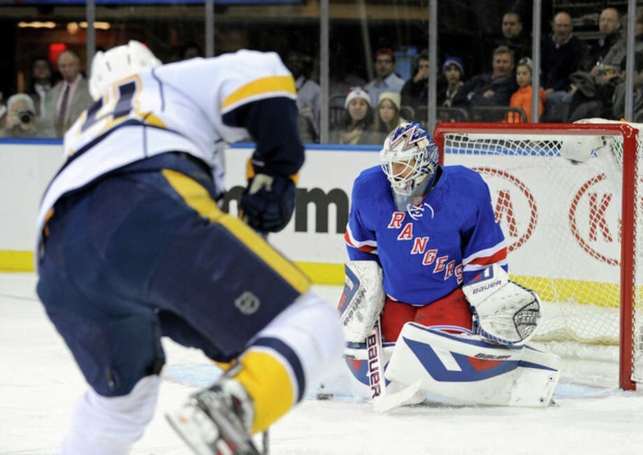 New York Rangers goaltender Henrik Lundqvist, right, of Sweden, makes a save during the first period of an NHL hockey game against the Nashville Predators Tuesday, Dec. 10, 2013, in New York. (AP Photo/Bill Kostroun) / FR51951 AP