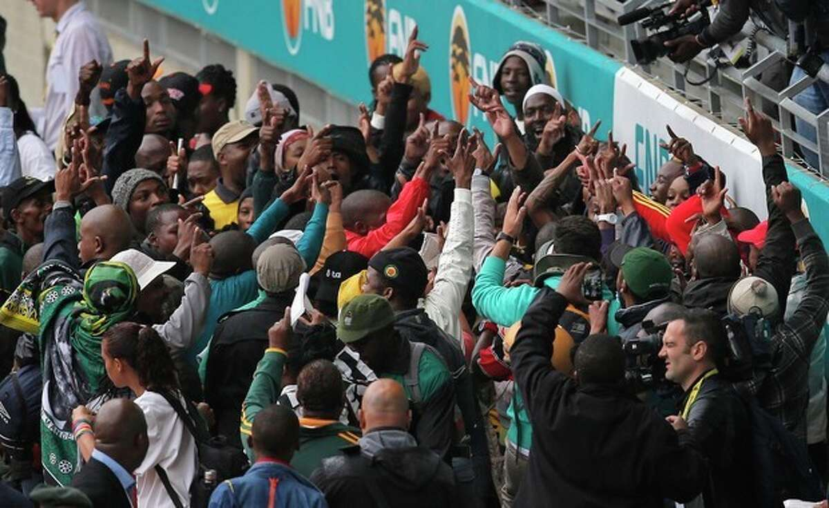 People dance as they arrive for the memorial service for former South African president Nelson Mandela at the FNB Stadium in Soweto, near Johannesburg, South Africa, Tuesday Dec. 10, 2013. Mandela died on Thursday Dec. 5, aged 95. (AP Photo/Peter Dejong)