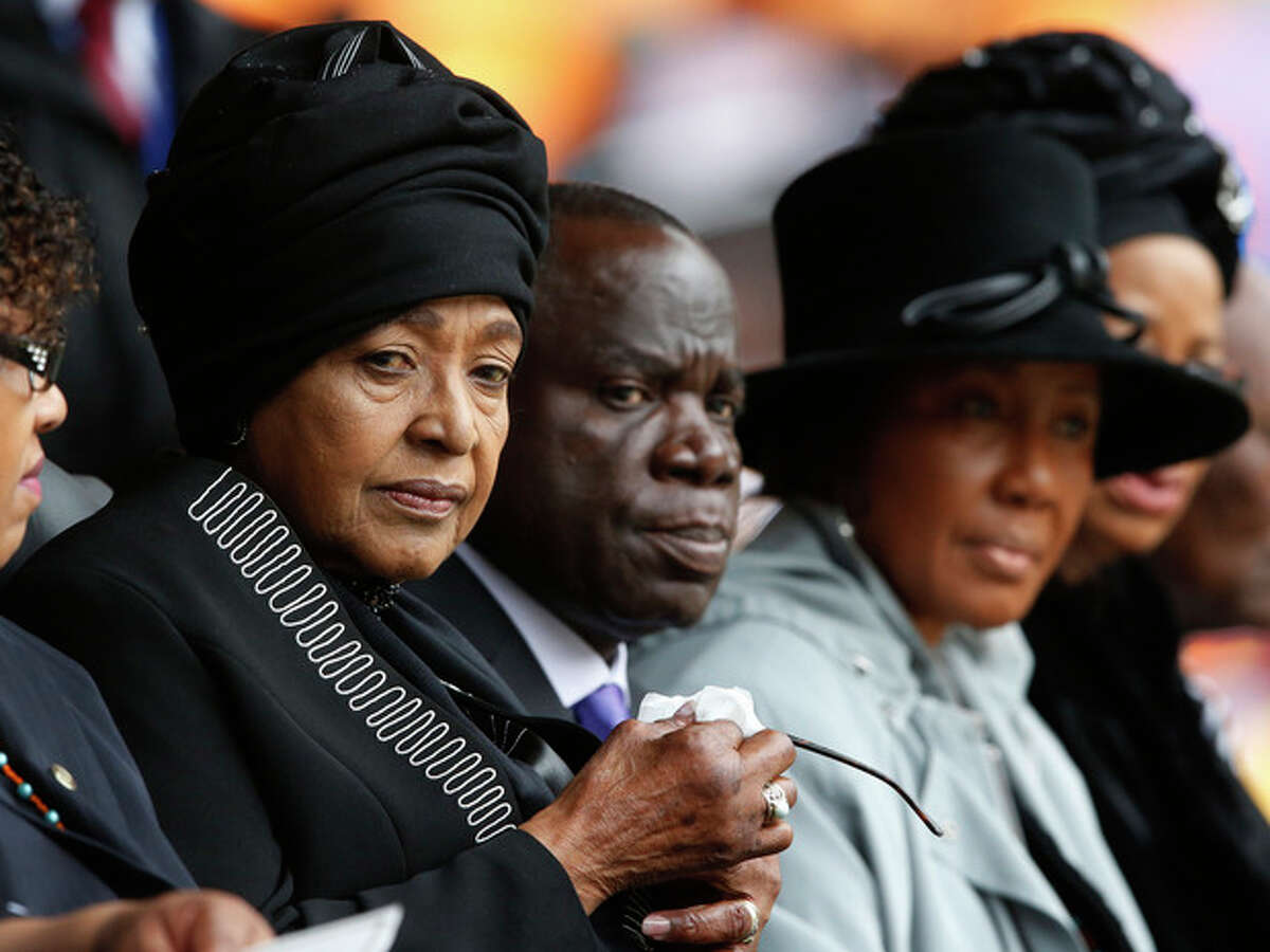 Winnie Madikizela-Mandela, left, Nelson Mandela's former wife, attends the memorial service for former South African president Nelson Mandela at the FNB Stadium in Soweto near Johannesburg, Tuesday, Dec. 10, 2013. (AP Photo/Matt Dunham)